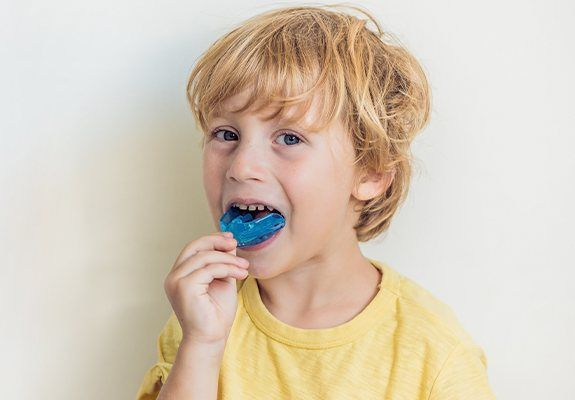 Young boy placing a blue mouthguard