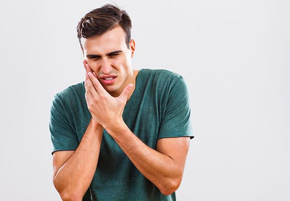 man in green t-shirt holding his mouth in pain