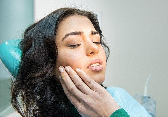 Woman in pain holding jaw