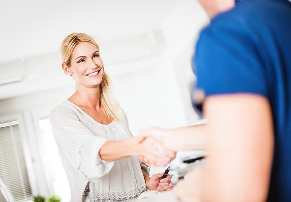 Smiling woman shaking hands with dental team member