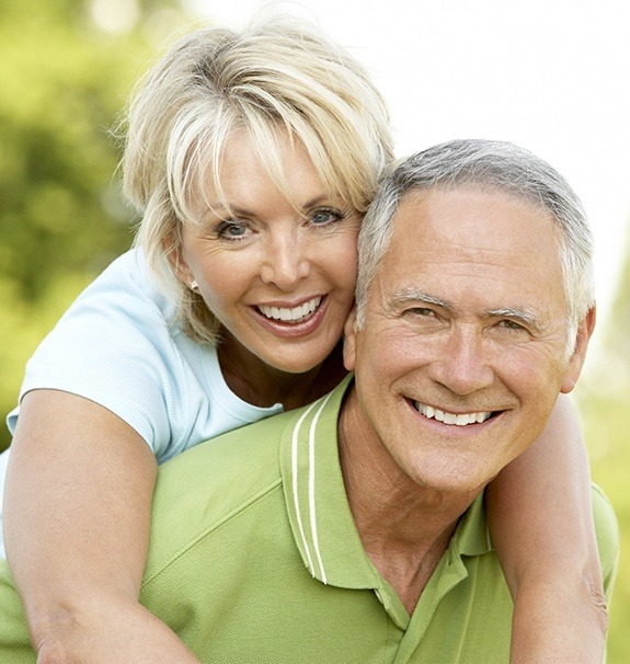 Older man and woman smiling after replacing missing teeth