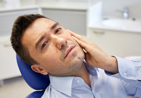 Man in need of tooth replacement holding jaw