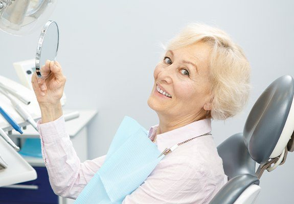 Woman looking at her new denture in hand mirror