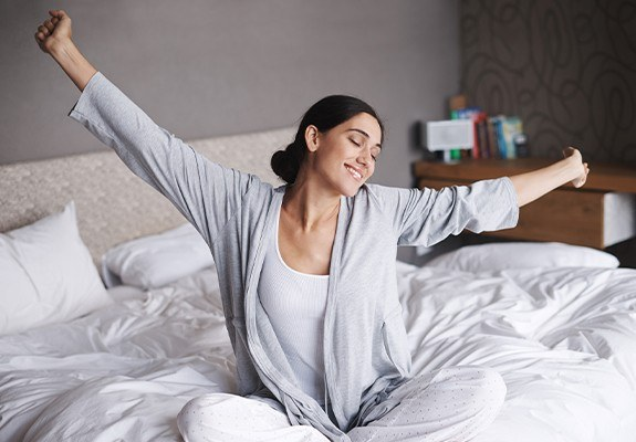 Woman waking feeling rested thanks to sleep apnea therapy