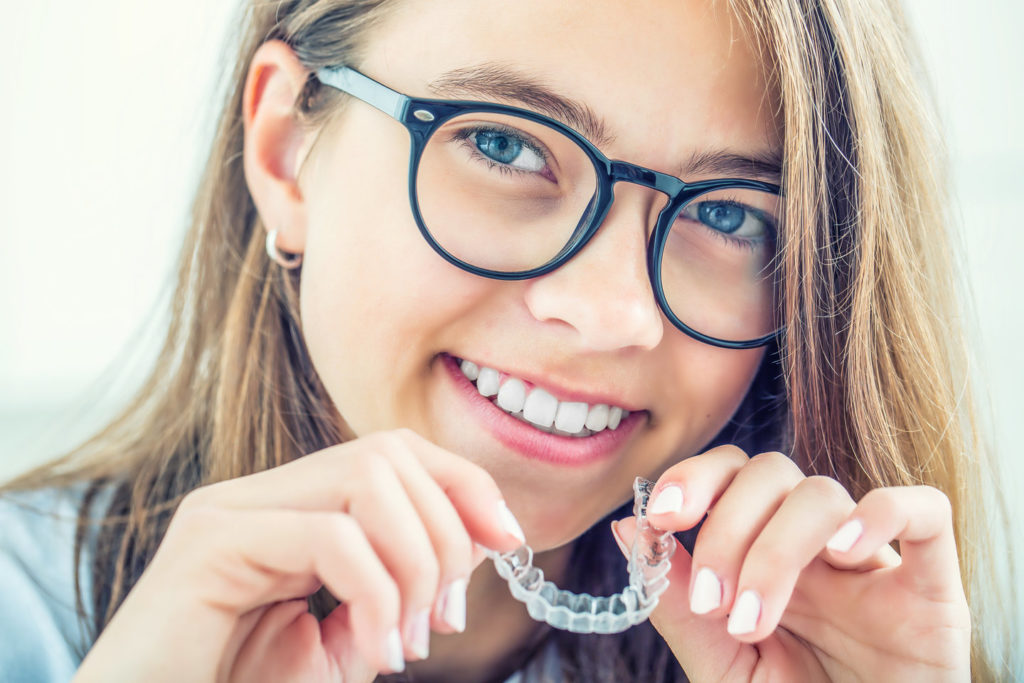Patient demonstrates Invisalign for teens in New Braunfels.